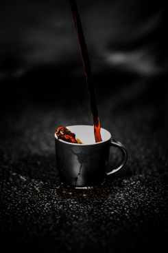 brown liquid pouring on black and white ceramic mug selective color photography